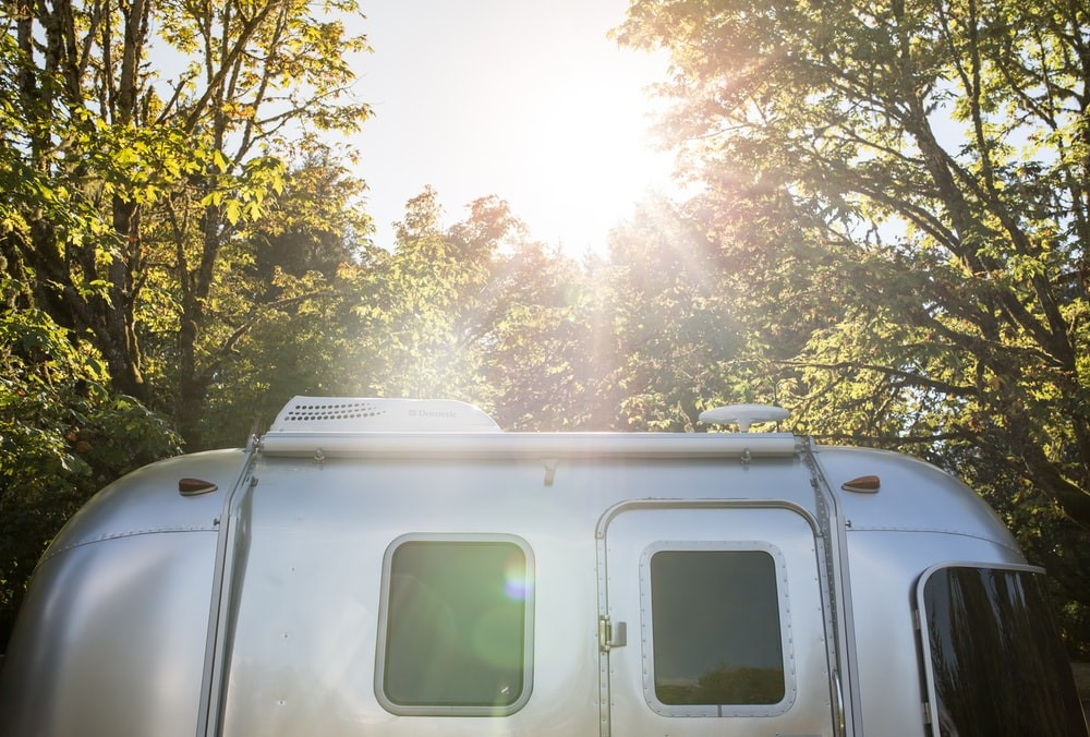 The Sun Shining Down on a Small Airstream Trailer Parked in the Woods